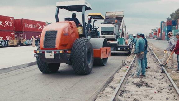 Concreto rolado sendo aplicado em uma estrada por um rolo compressor.
